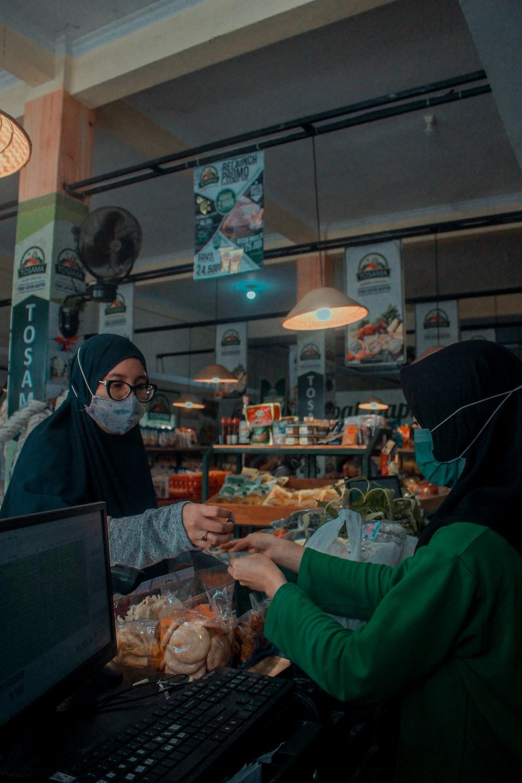 woman in green long sleeve shirt standing near woman in black hijab