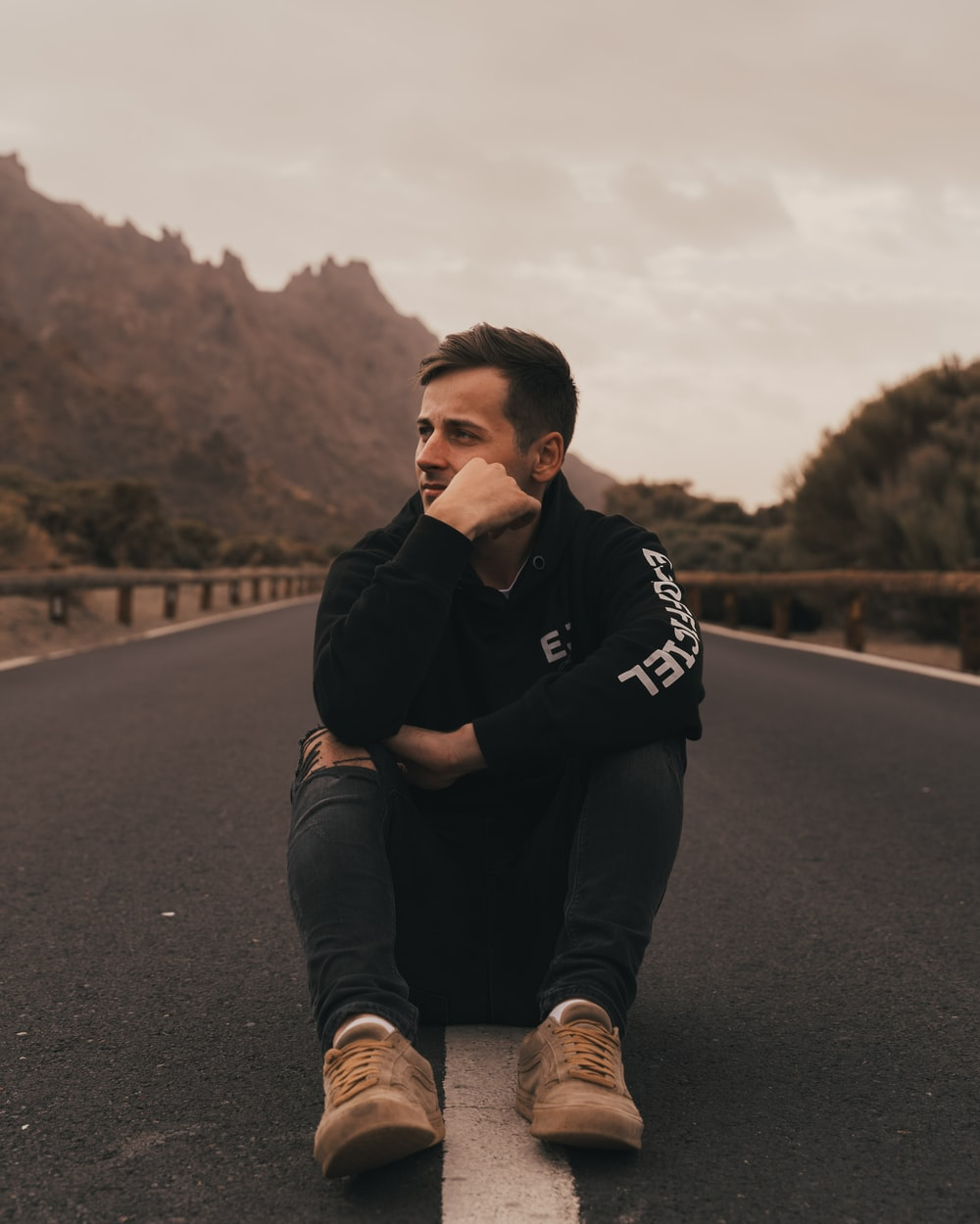 man in black and white hoodie sitting on the road during daytime
