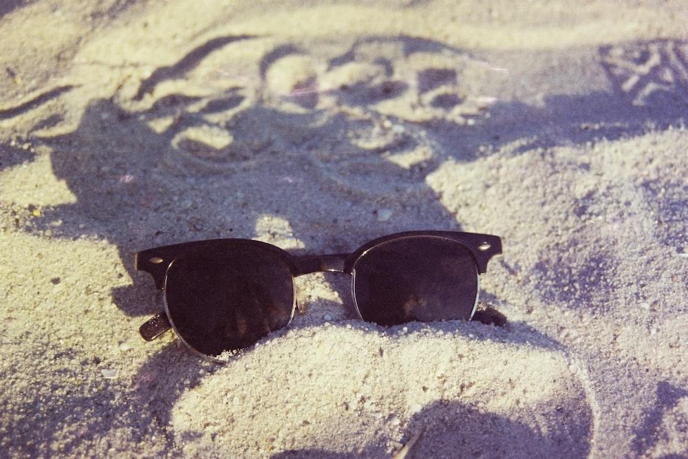 black framed sunglasses on white sand