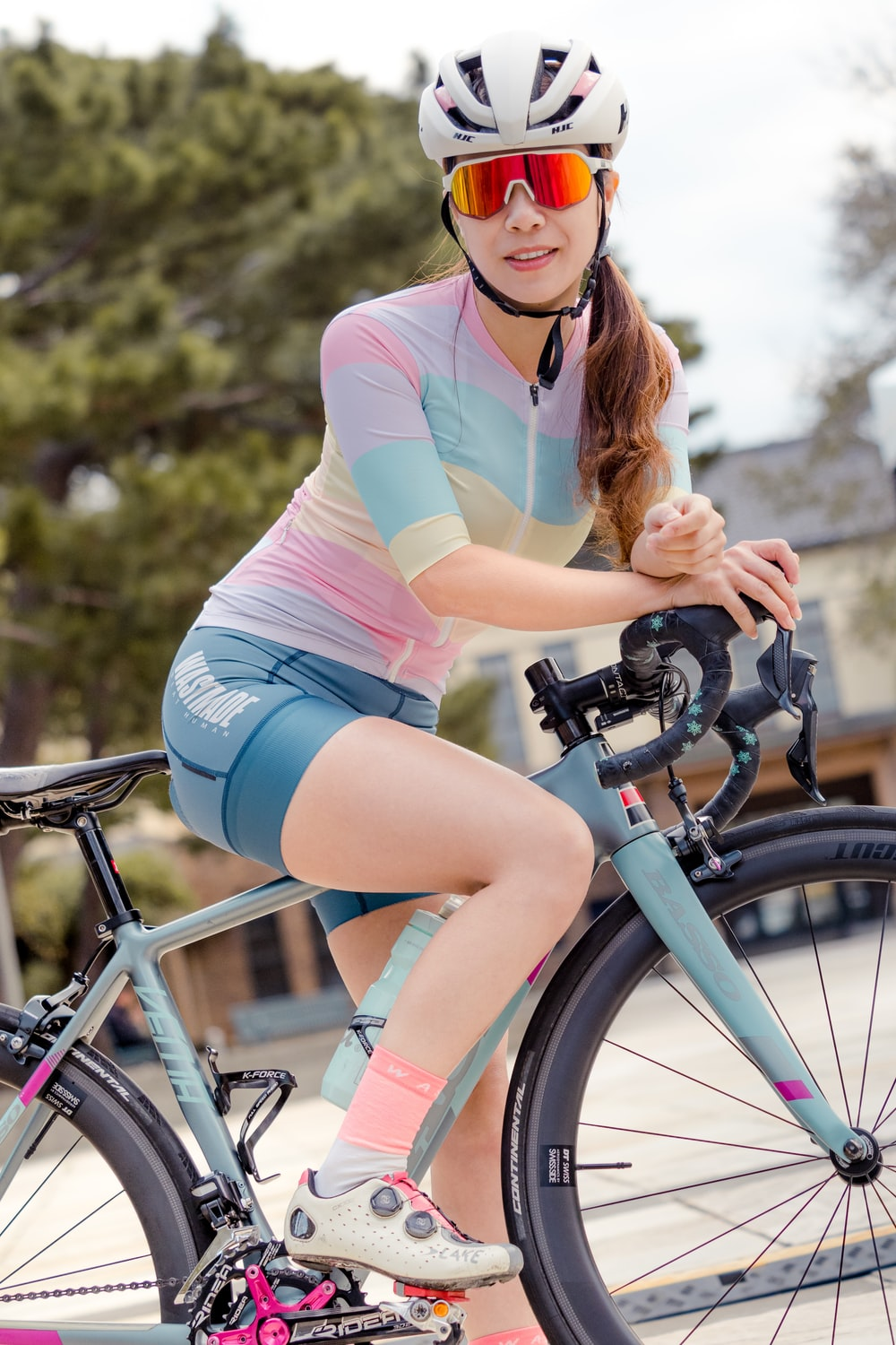 woman in pink shirt and blue shorts riding on black bicycle