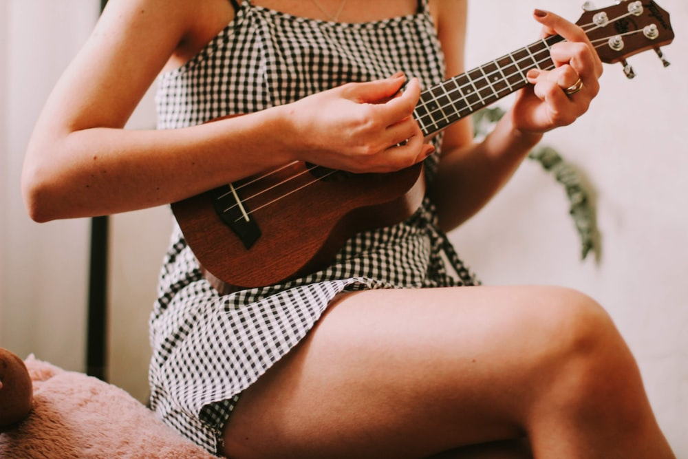 woman in black and white checkered sleeveless dress playing brown acoustic guitar