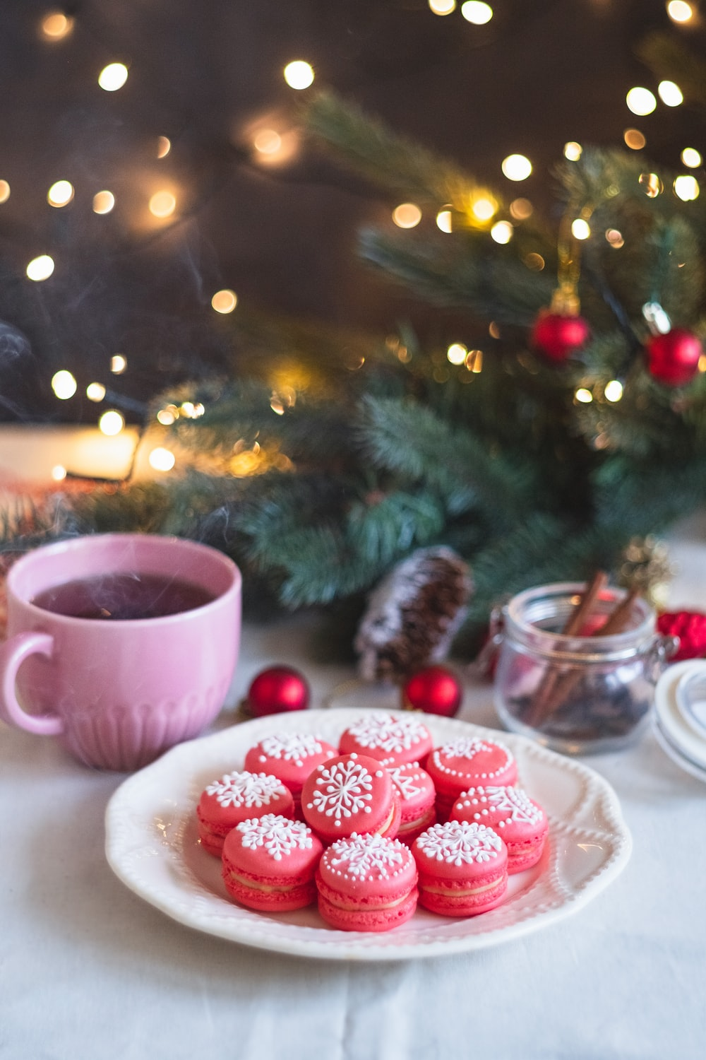 pink ceramic mug beside clear glass bowl with red round fruits