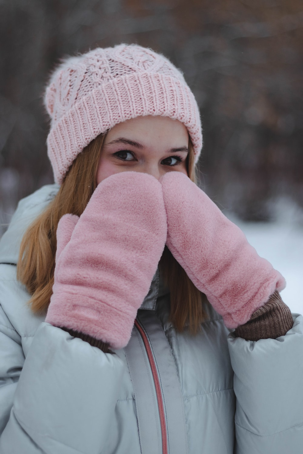 woman in white jacket and pink knit cap