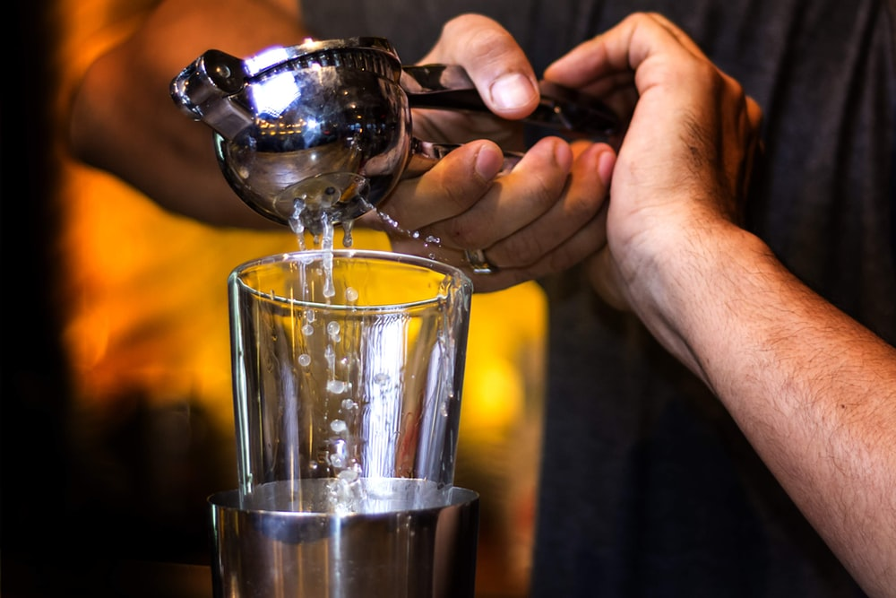 person pouring water on clear drinking glass
