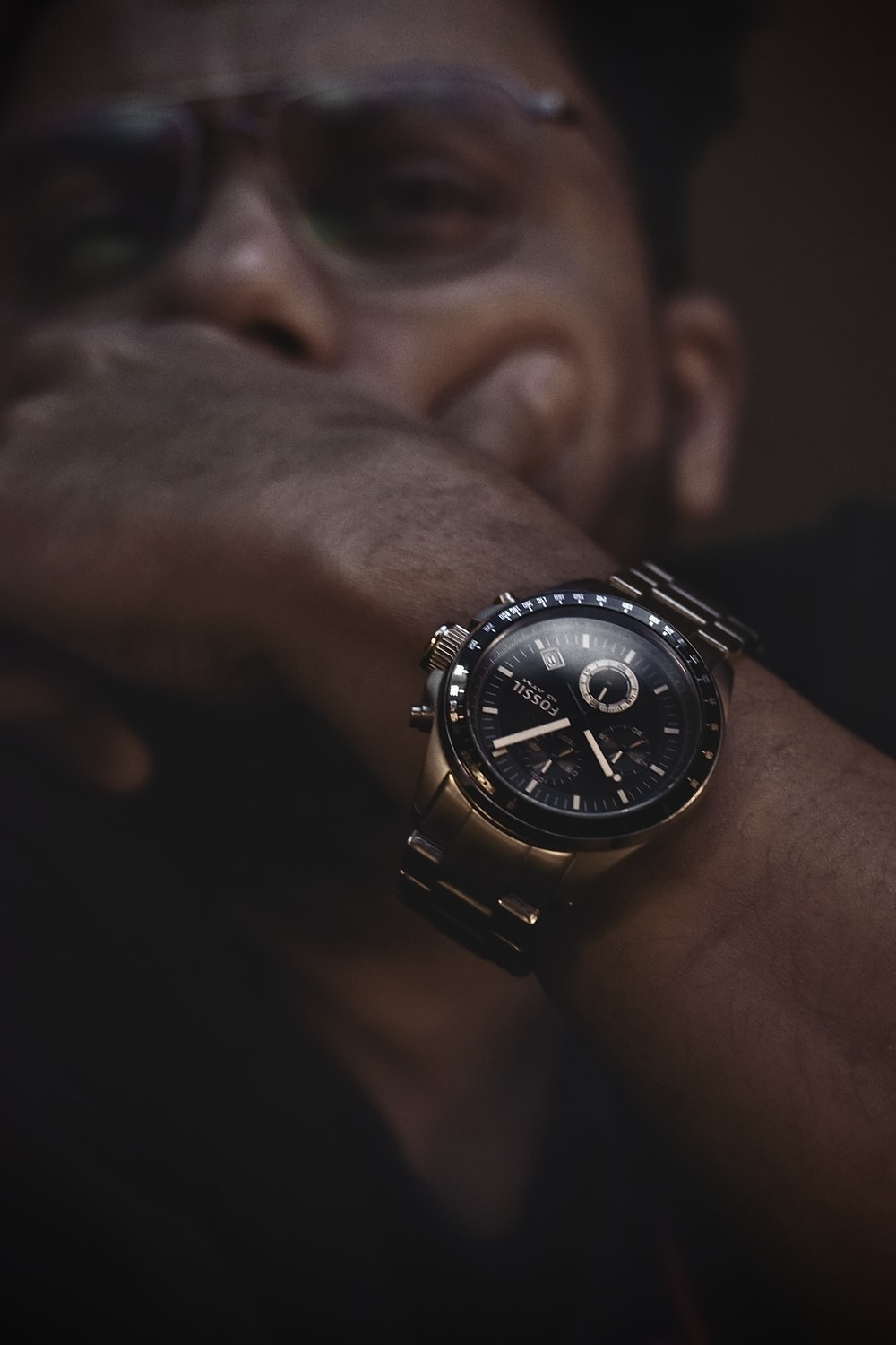 person wearing black and silver round chronograph watch