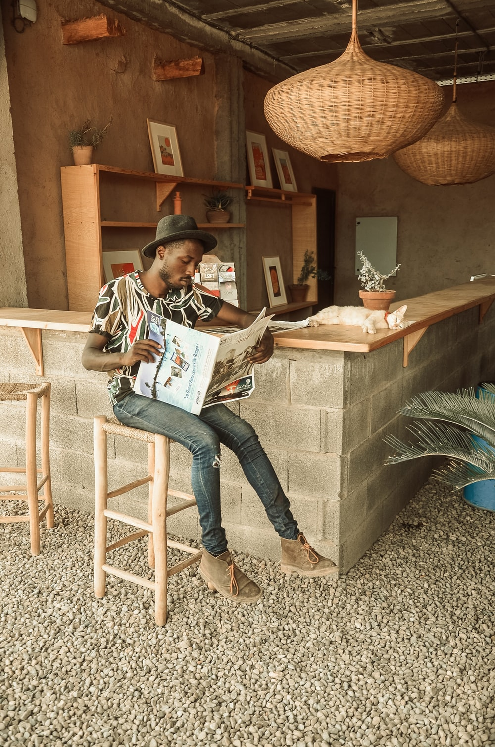 woman in blue denim jeans sitting on brown wooden chair reading book