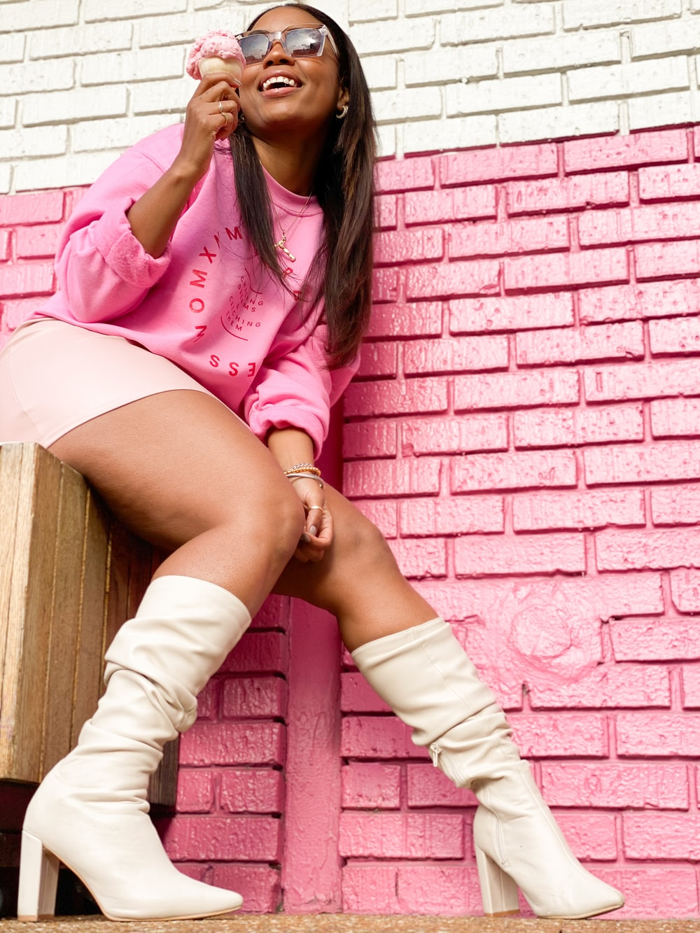 woman in pink and white striped long sleeve shirt and white skirt sitting on brown wooden