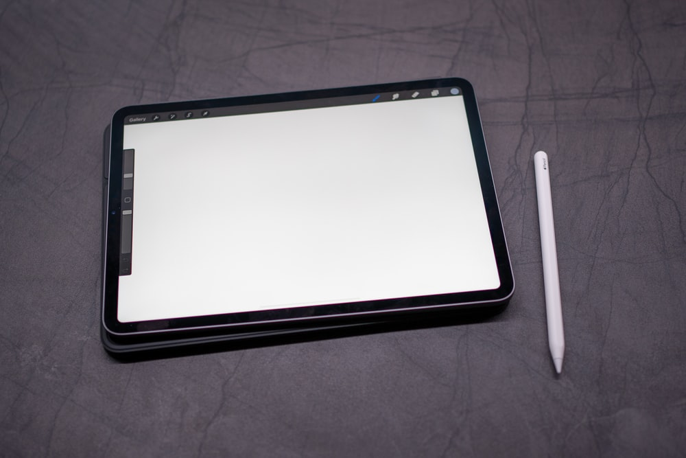 black tablet computer on gray textile