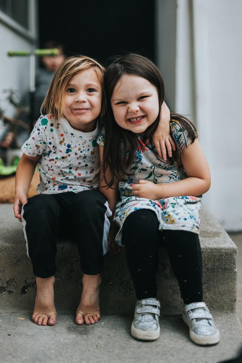 2 girls sitting on concrete floor