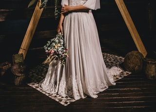 woman in white floral dress standing on brown wooden ladder
