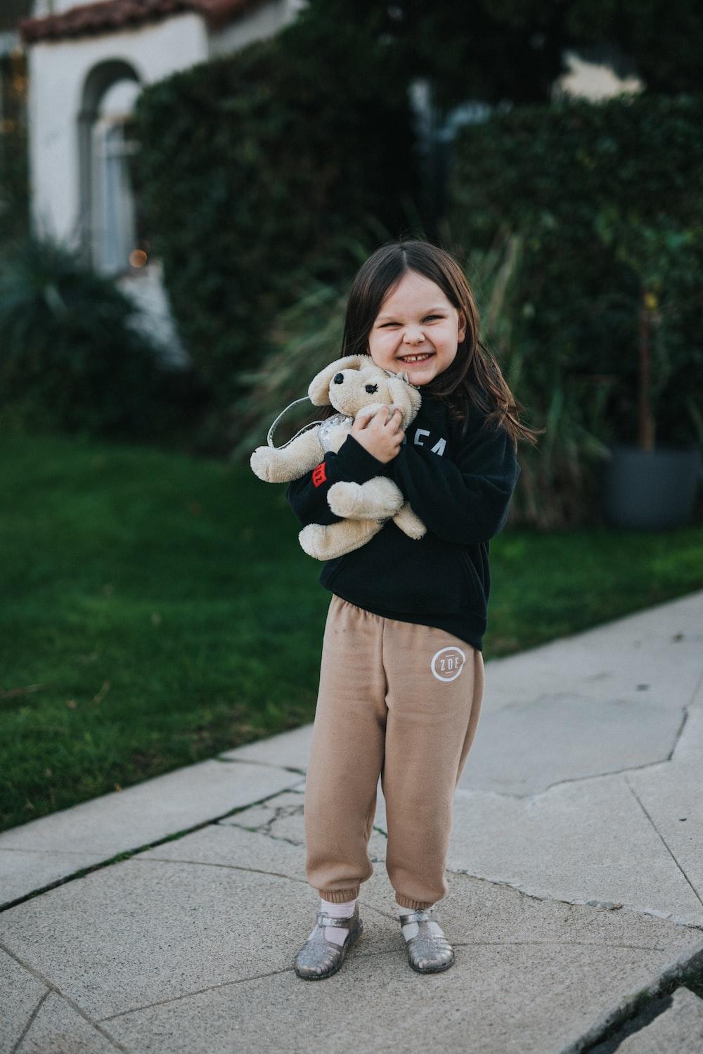girl in black long sleeve shirt holding white bear plush toy