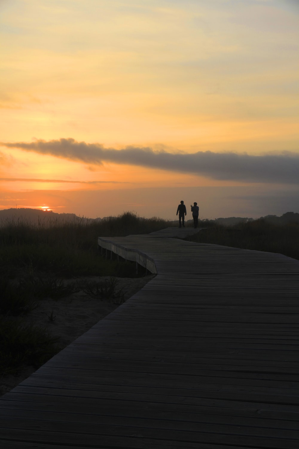 silhouette of 2 person walking on pathway during sunset