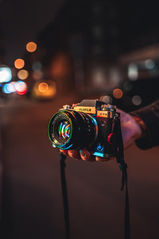 person holding black and silver nikon dslr camera