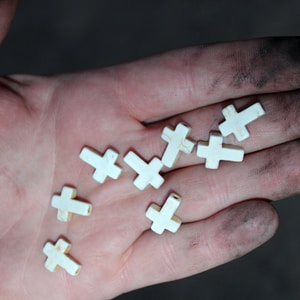 person holding 4 white cross
