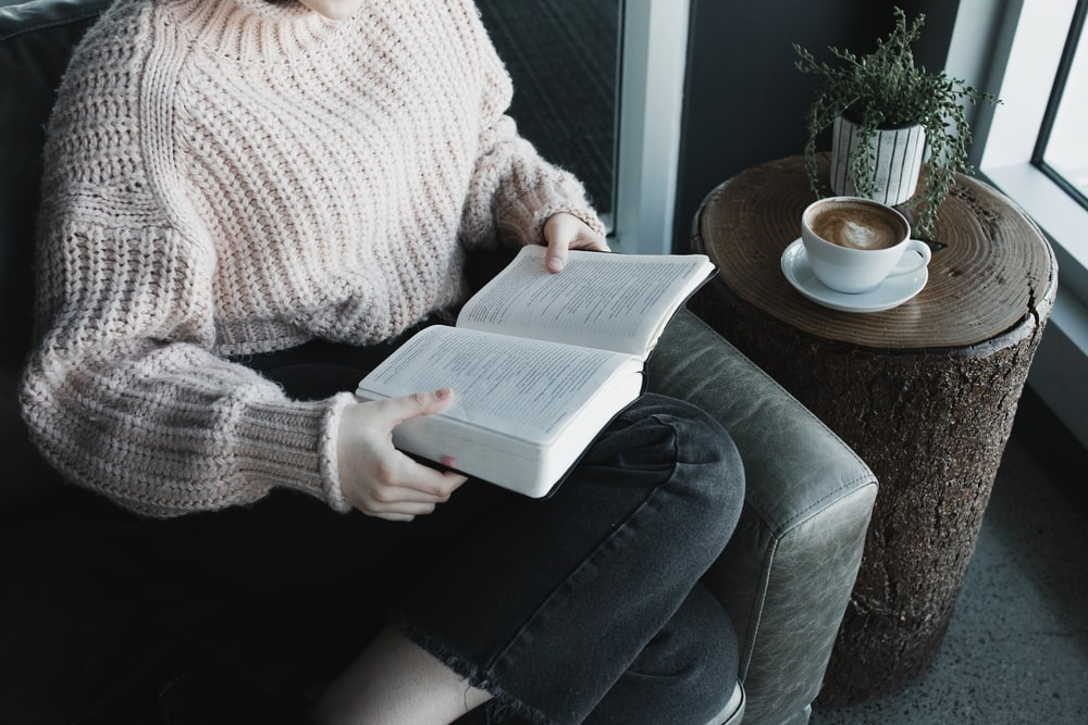 woman in white knit sweater and blue denim jeans sitting on gray couch reading book
