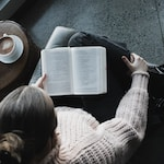 woman in white sweater reading book