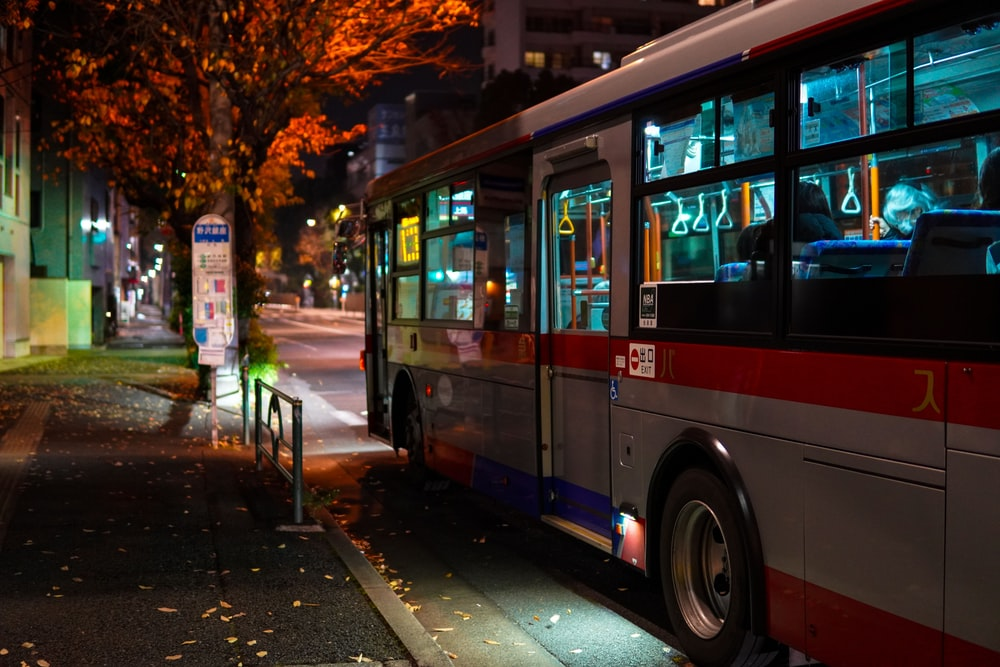 red double decker bus on road during night time