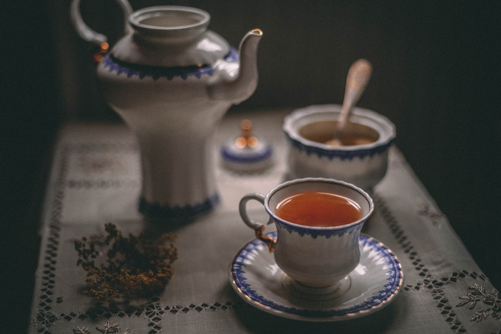white ceramic teapot beside white ceramic teacup on saucer