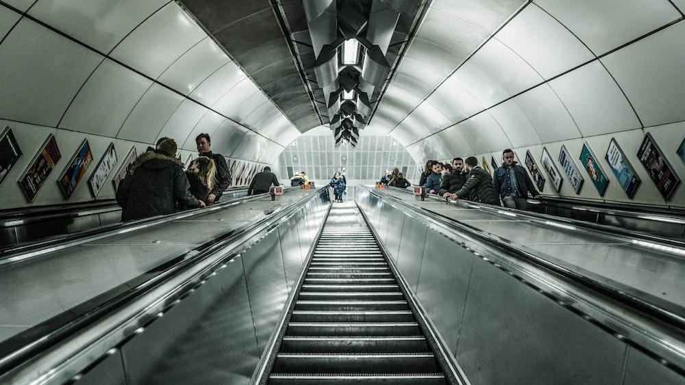 people walking on escalator inside building