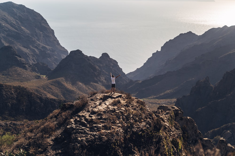 person standing on brown rock mountain during daytime