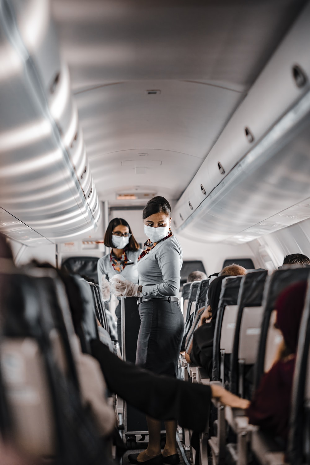 air hostess wearing a facemask standing in the aisle of an aeroplane