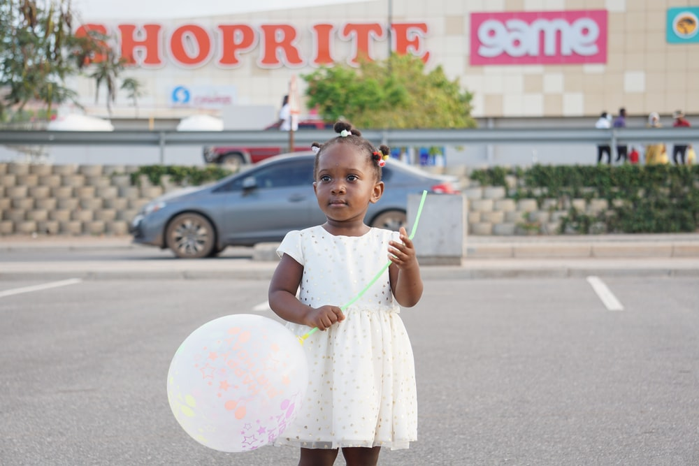 girl in white dress holding white and pink balloons