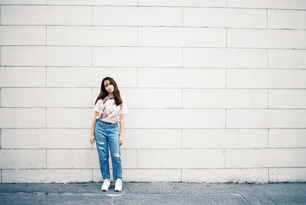 woman in white shirt and blue denim jeans standing beside white wall