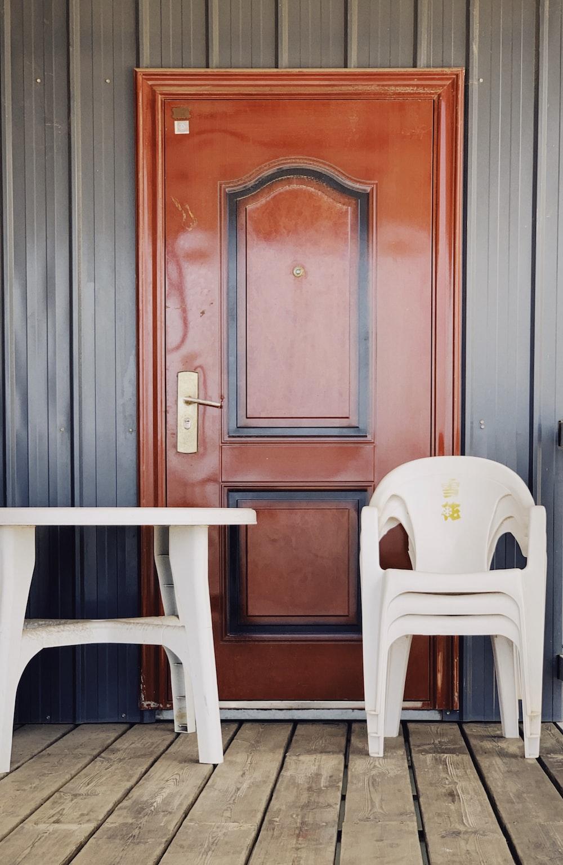 white plastic chair beside blue wooden door
