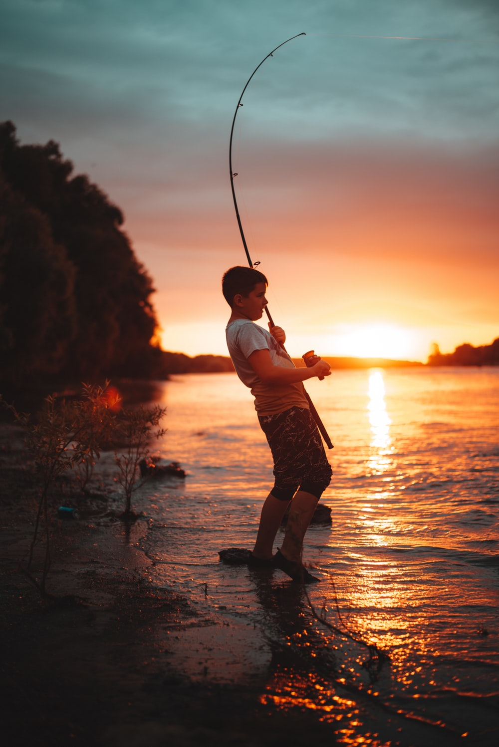 boy in white shirt and brown shorts holding fishing rod during sunset