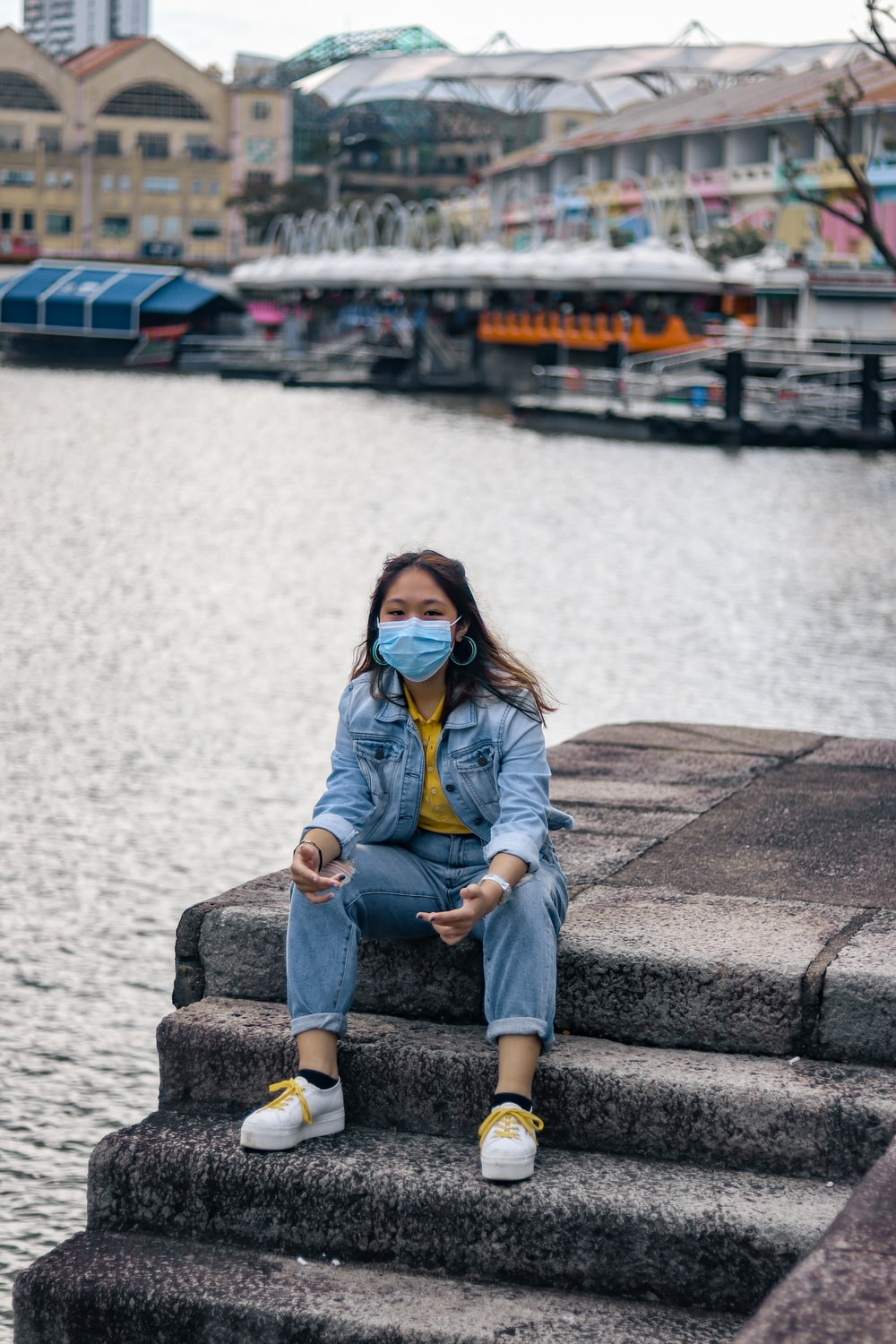 woman in blue denim jacket and blue denim jeans sitting on concrete bench