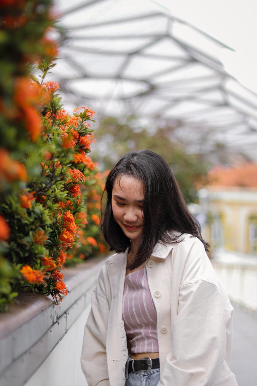 woman in white long sleeve shirt standing beside orange flowers