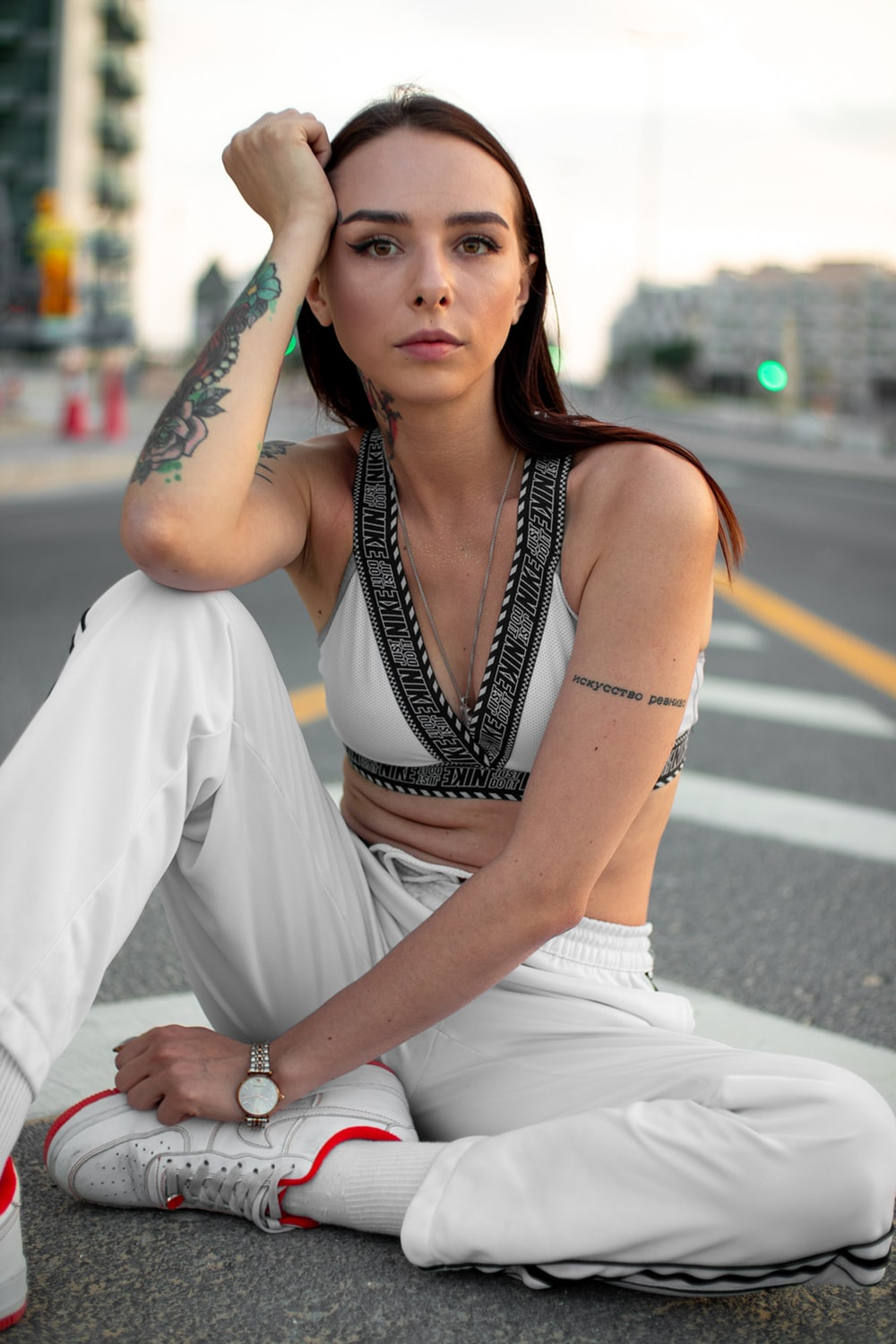 woman in white sleeveless dress sitting on road during daytime