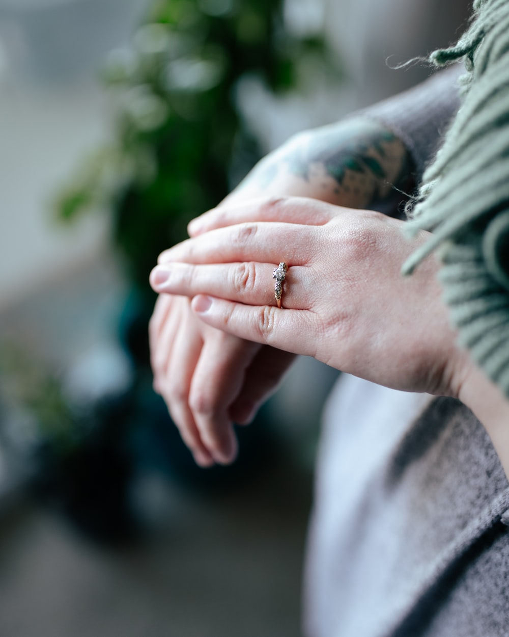 person in gray long sleeve shirt holding silver ring