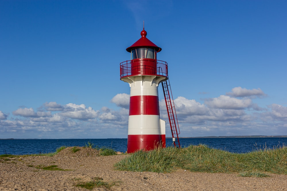 red and white lighthouse on green grass field under blue sky during daytime