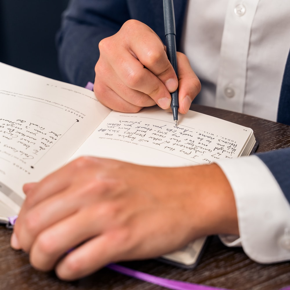 person in blue suit holding pen writing on white paper