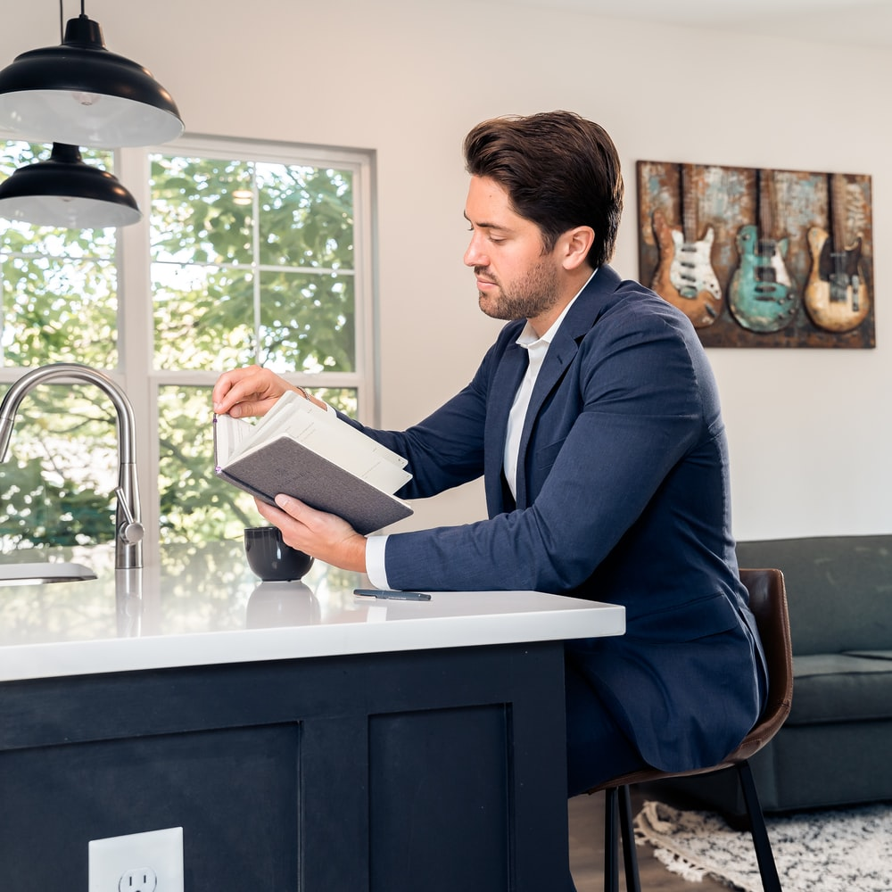 man in blue suit jacket reading book