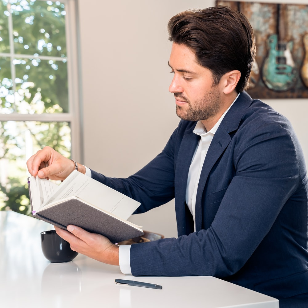 man in blue suit reading book