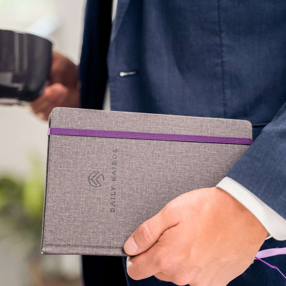 person holding purple book during daytime