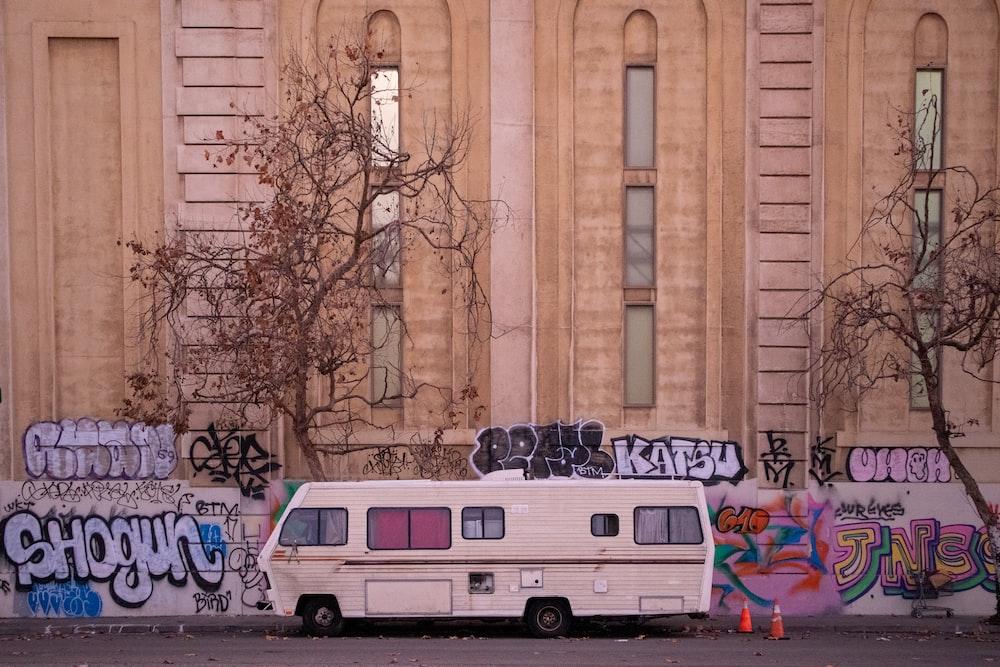 white van parked beside brown building