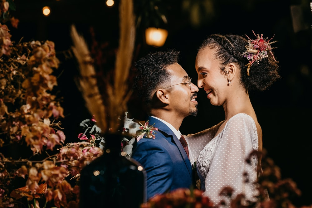man in blue suit kissing woman in white floral dress