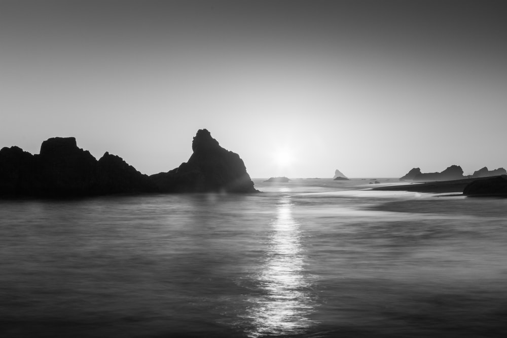 grayscale photo of rock formation on sea
