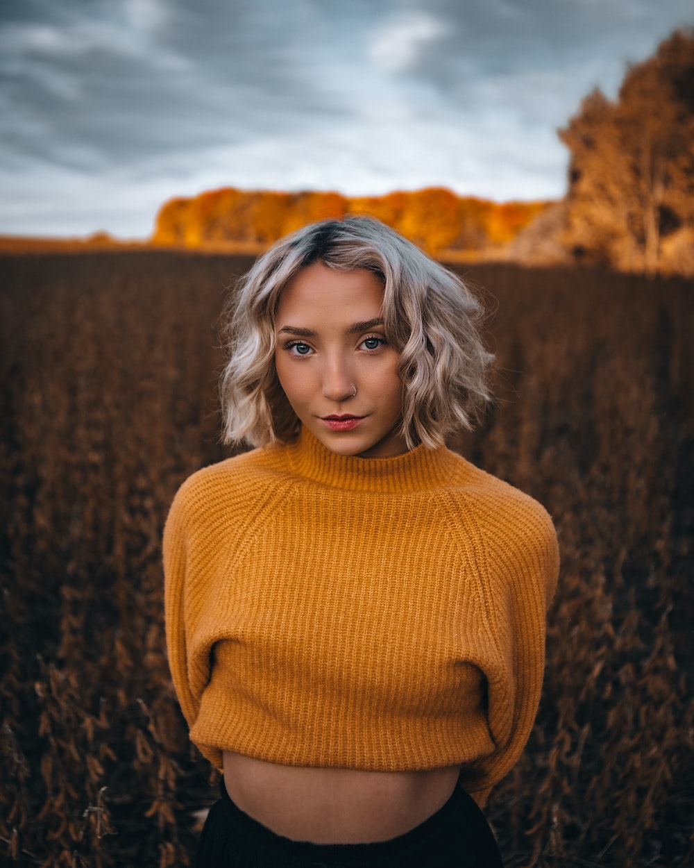 woman in brown turtleneck sweater standing on brown grass field during daytime