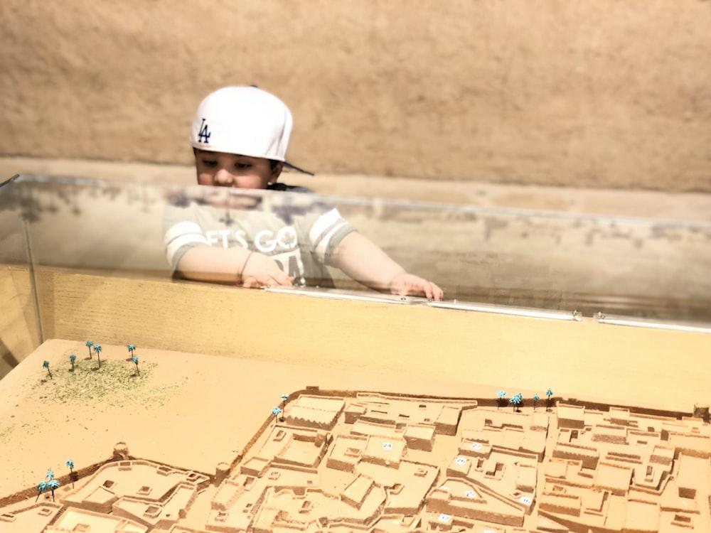child in white helmet lying on brown sand during daytime