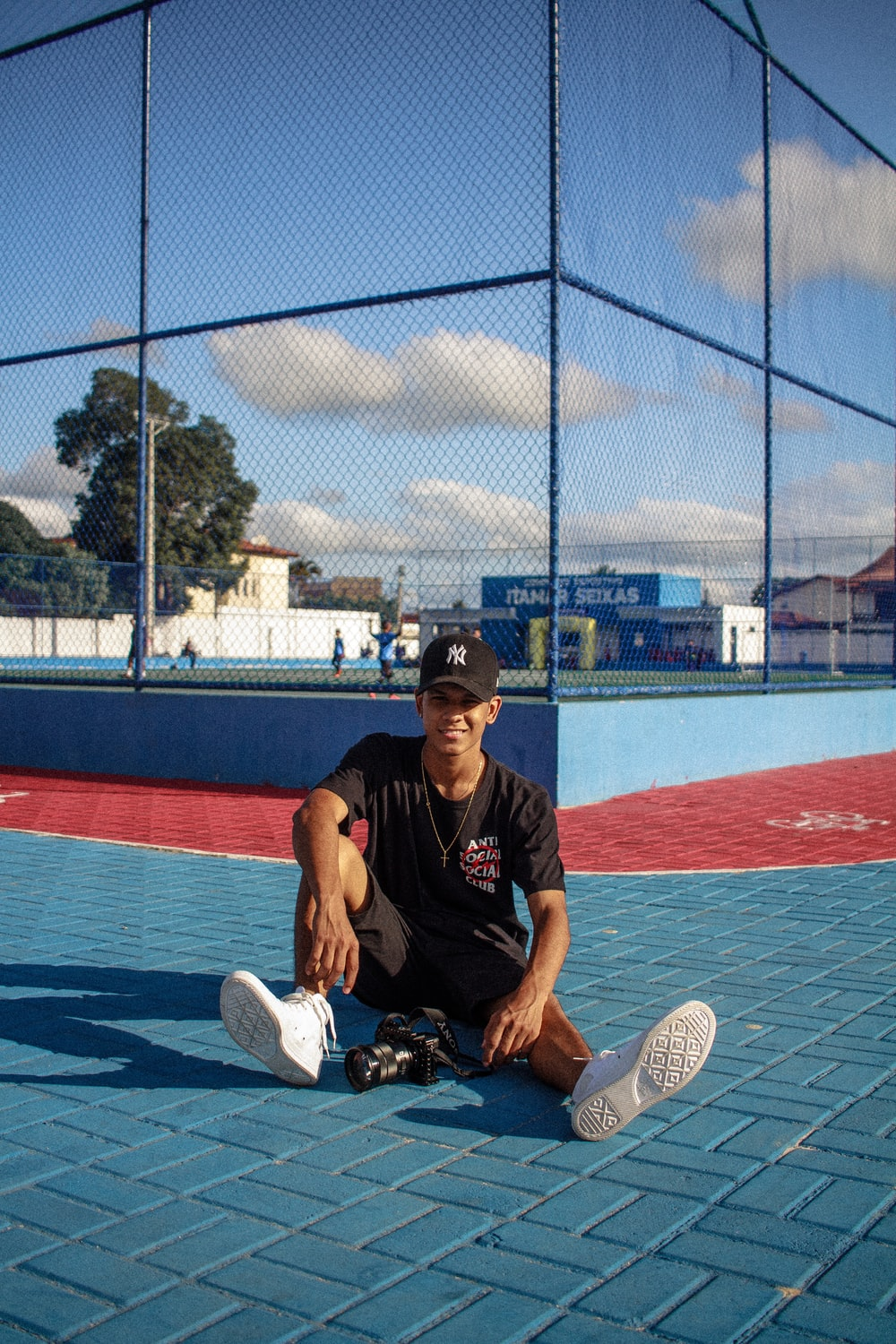 man in black crew neck t-shirt and black pants sitting on tennis court