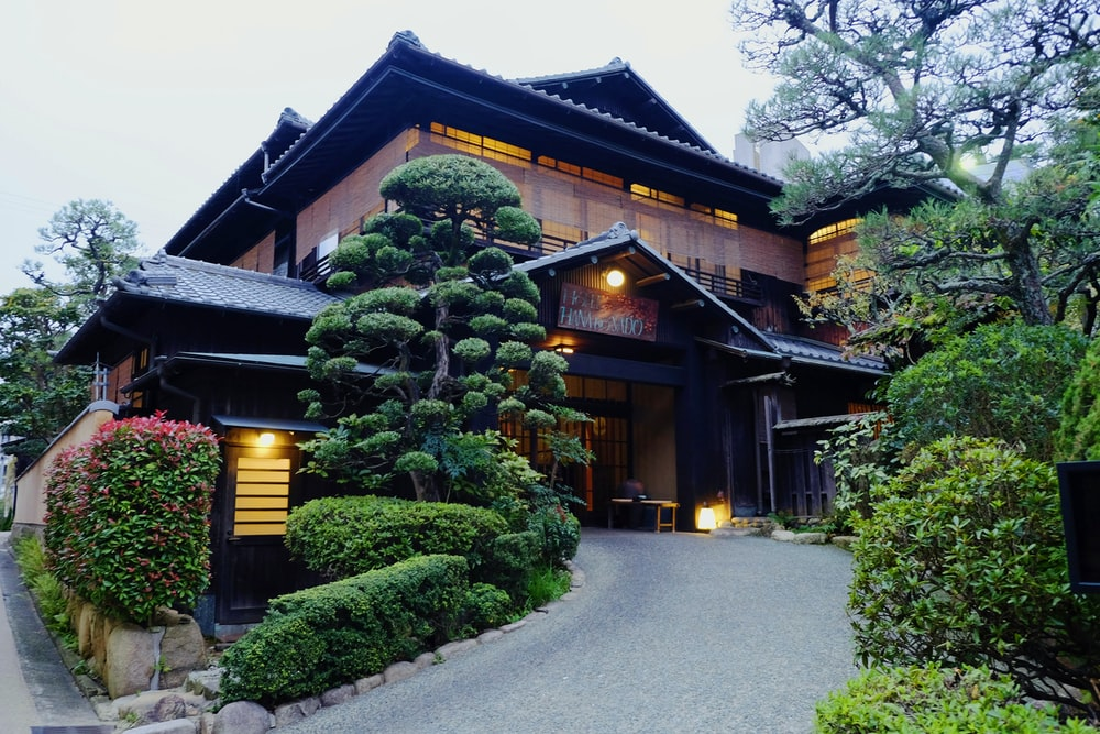 brown and black wooden house near green trees during daytime