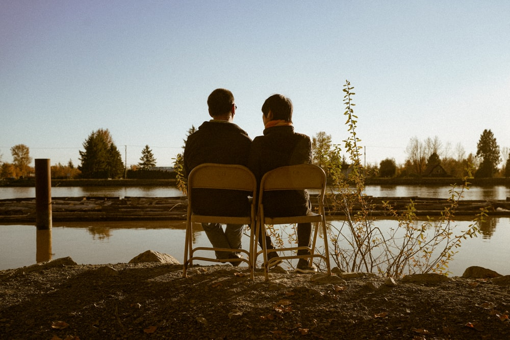 couple sitting on black folding chairs near lake during daytime
