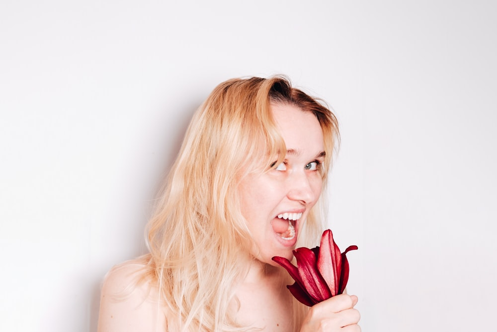 blonde woman holding red tulip