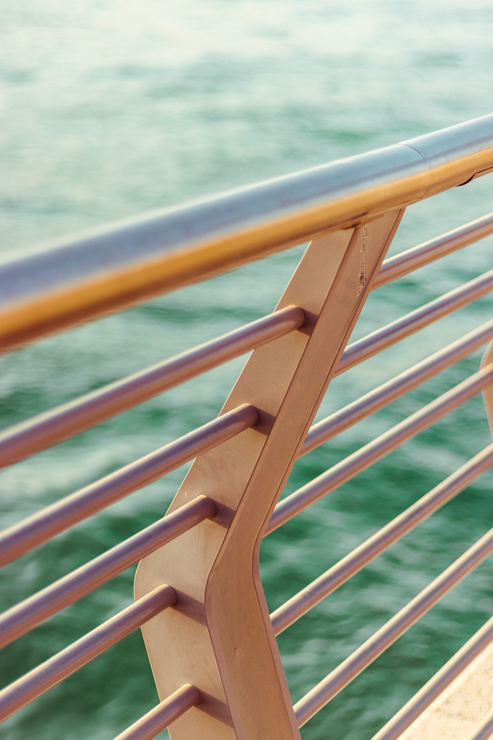 brown wooden railings near body of water during daytime