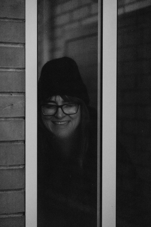 woman in black knit cap and black framed eyeglasses