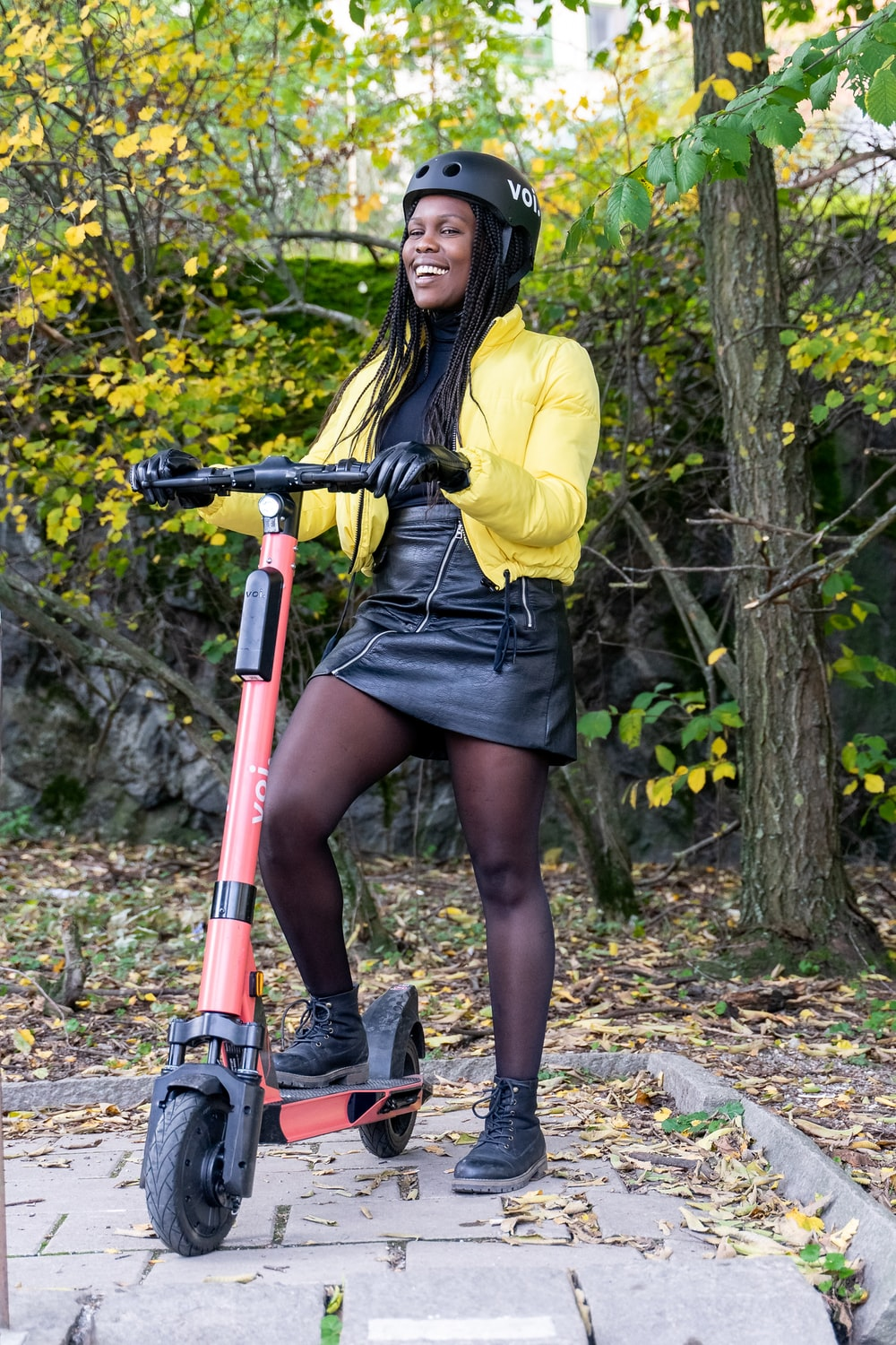 woman in yellow long sleeve shirt and black skirt holding red and black bicycle